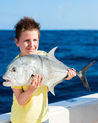 boy proudly holding a fish caught while deep sea fishing